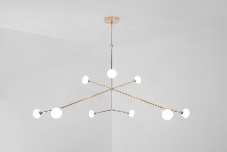 The Super Nova chandelier is centerpiece fixture with an elegant and energetic composition. This contemporary chandelier branches out from a central point in a pure, geometric manner. It features nine white glass shades that house powerful, dimmable