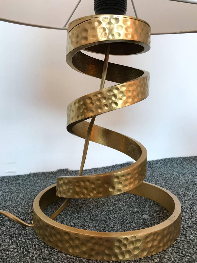 Spiral pair of table or bedside lamps by the designer Luciano Frigerio. Hammered brass maybe bronze. Measurement Height feet 29 centimetres. Note: Demonstration shades not included. Famous designer like Angelo Brotto, Esperia, Tommaso Barbi.