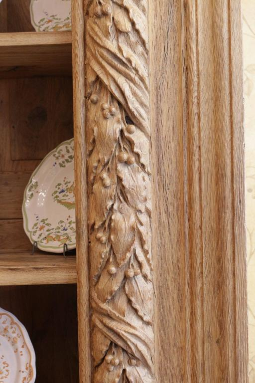 Oak display cabinet from a palatial paneled library room the 18th century front show a very fine and impressive laurel carving.  It has been transformed as a book case, late 19th century.  The front, the sides, the paneled back and the shelves are