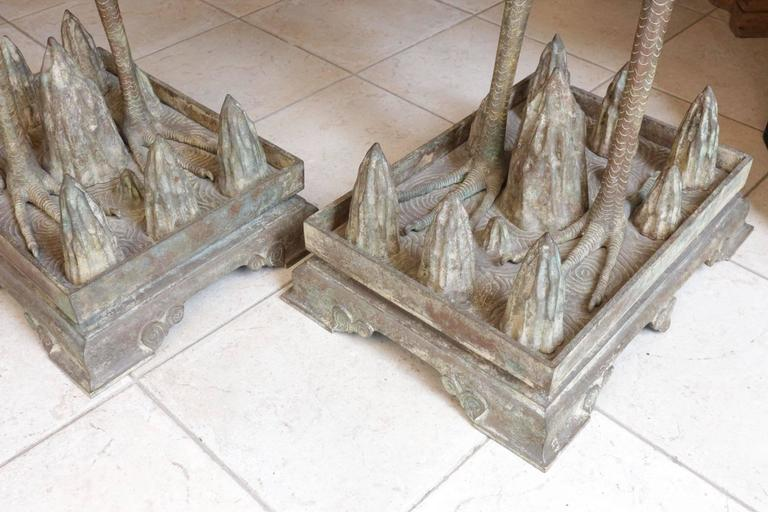 The cranes are standing on a rectangular plinth with their heads raised They are naturalistically cast with detailed feathers on wings and legs, the base is surmounted by numerous small peaks  Symbolizing longevity, the crane has always been an