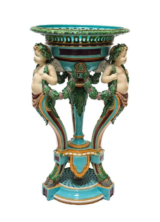 A Minton England majolica jardiniere featuring three faun footed cherubian figures serving as pillars supporting a reticulated planter top. Each winged cherub connected with a ribboned vine leaf draped around their neck.  Impressed marks for