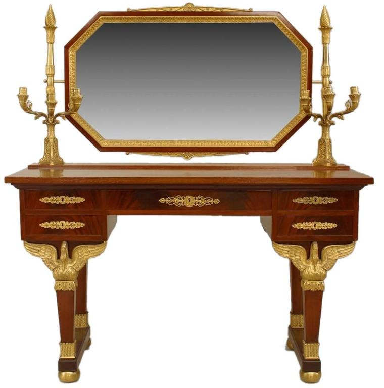 From the third quarter of the 19th century, a Second Empire lady's dressing table with elegant gilt bronze swan supports mounted to legs, octagonal shaped tilting mirror and three arm candelabras at each end. Four drawers, two presumably for