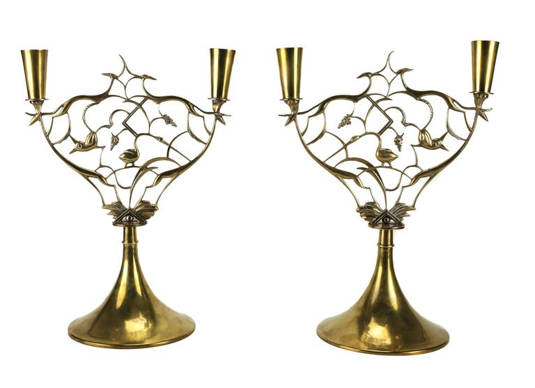 A stunning pair of brass candlesticks with intricate animal integrated vines and grape vine clusters by Karl Hagenauer and produced by Werkstatte Hagenauer. Each signed WHW in a circle.