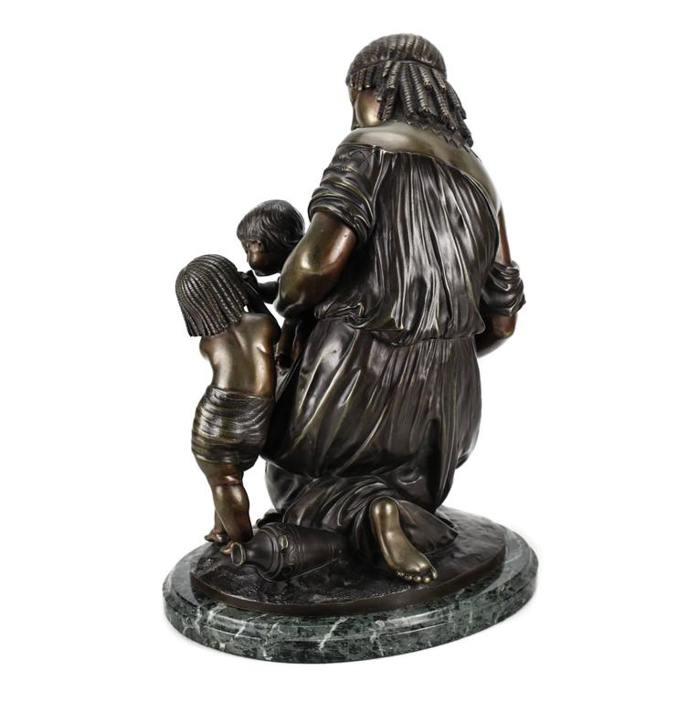 A lovely Egyptian revival bronze sculpture of a kneeling woman holding a clam shell with an infant and toddler sharing a drink of water. A fine quality cast after the original model by Francois Moreau, patinated light and dark brown with polished