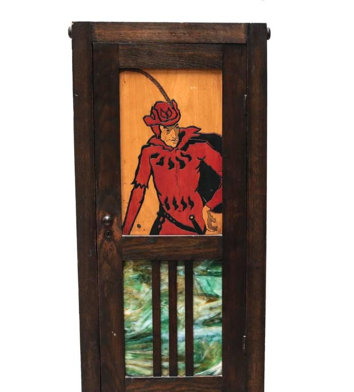 An unusual early 20th century stained oak cabinet, the front door set with a colorful slag glass panel and with a painted and engraved figural depiction of a musketeer or Robin Hood type on an inset panel of maple wood.   Opens to reveal a three