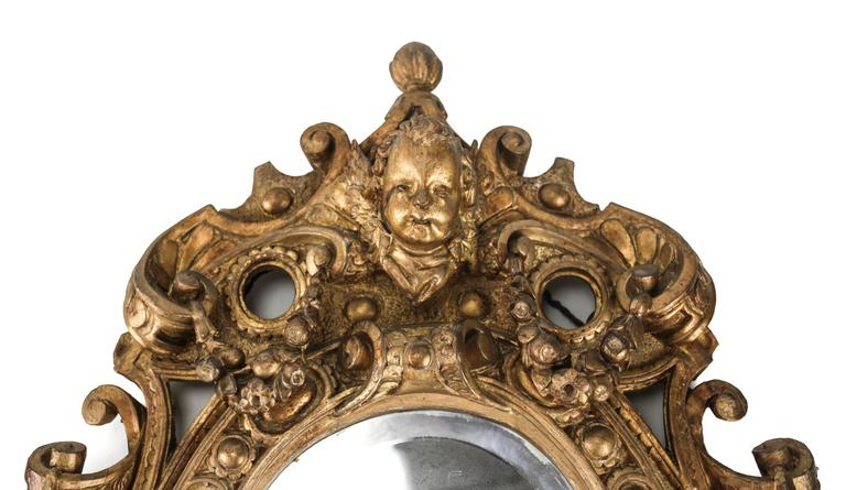 An attractive pair of oval giltwood mirrors from the late 18th century, each hand-carved with an intricate decoration of floral swags, ribbons and open work, the head of a winged cherub stationed atop each.  Previously purchased from Christie's in