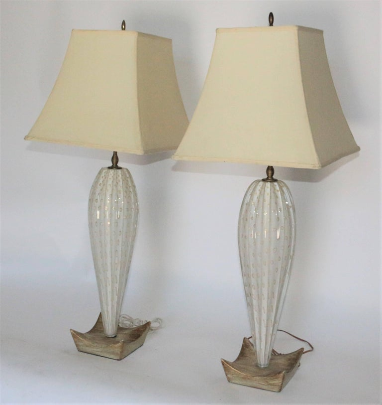 """Pair of tall Italian Mid-Century Modern Murano lamps with a Ribbed glass and gold Bullicante. Wooden base and gold accents. Shade measurements: 13"""" H - 15"""" bottom opening. 8.5"""" top oppening."""