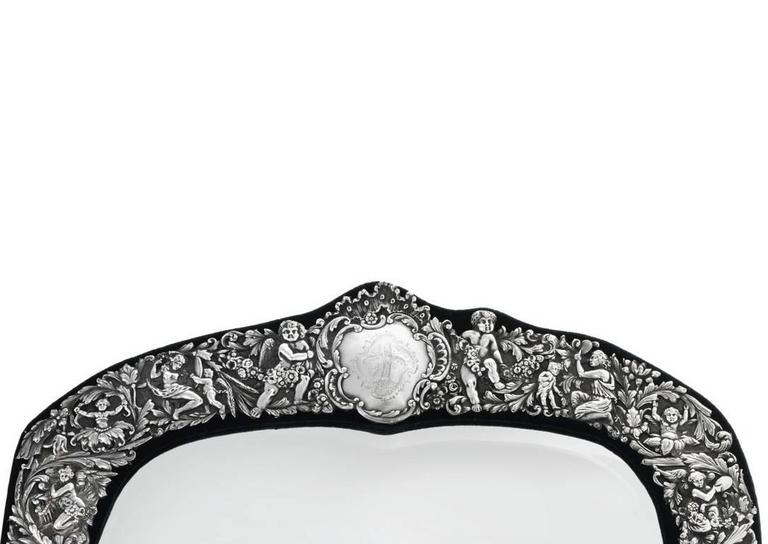 A large sterling silver cast and chased border decorated mirror frame mounted on a green velvet wrapped wood back with hinged Stand. Depicting foliage and grotesques, the top centered by a Rococo cartouche engraved with coat of arms and flanked by