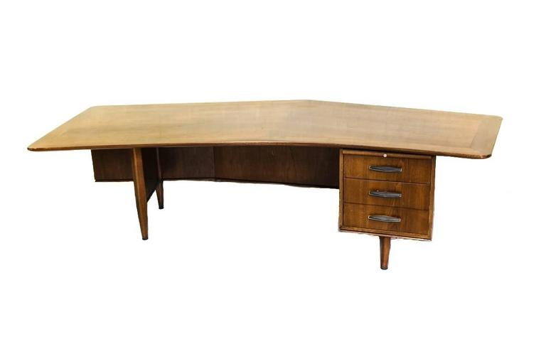 A large Mid-Century walnut executive desk by Monteverdi Young. Off-center peaked front in the boomerang style, inlaid wood trim and three compartment drawers with slant angled handles. Original paper label inside top drawer.