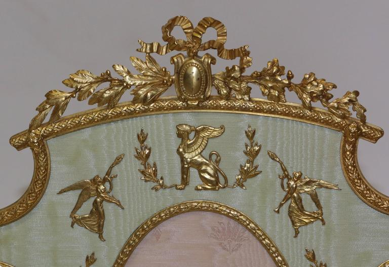 French multi picture ormolu frame. The figurines inside of the frame are made of bronze ormolu with great attention given to detail. The stand is made of bronze ormolu as well. This elegant item holds seven picture within the ormolu etched frames.
