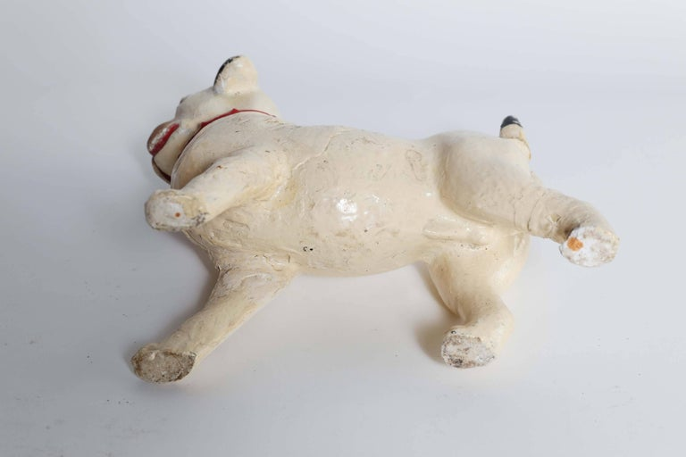 For the lover of pugs, a vintage glazed plaster statue from France. This adorable fellow with a cream, black and brown body sports a red collar, a proud stance and a precious face. There has been a repair at the tail that takes nothing away from the