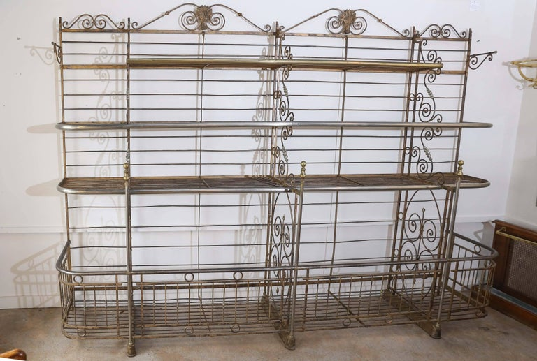 A truly outstanding bakers rack marked 'Lyon, France'. Grand in scale, this iron and brass rack has a large open gallery at the bottom with three tiers above. Intricate scroll work adorns each section and brass wheat medallions embellish the top.