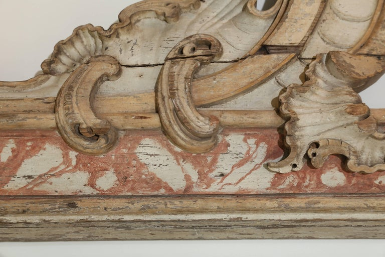 Traces of pale grey, dark grey and terracotta paint over light wood tones accent the carving on this splendid and unusual architectural element from France. Hangers are attached.