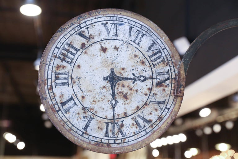 A unique and utterly charming sign from a clockmaker's shop in France. Made of iron and sheet metal, the 12 inch clock face is supported on a 28 inch iron bracket with a leaf embellishment. One side of the sign is beautifully aged and worn while the