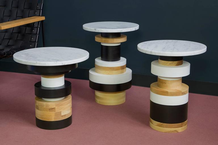 """The Sottsass-inspired """"Sass Tables"""" are simple, sculptural accents for any interior space. Made from stacked wooden bases and a honed marble top, Sass tables are perfect individually or clustered. Measures: 18 inches tall with 18 inch marble top."""