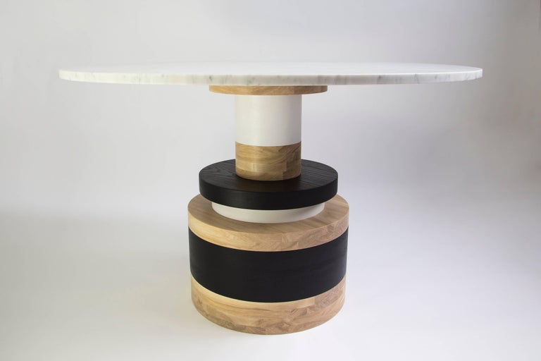 "The Sottsass-inspired ""Sass Dining Table"" is a bold, graphic statement piece. A polished Nero Marquina marble top sits on an Amish-made base composed of painted and stacked wood circles.   The version as shown is 54"
