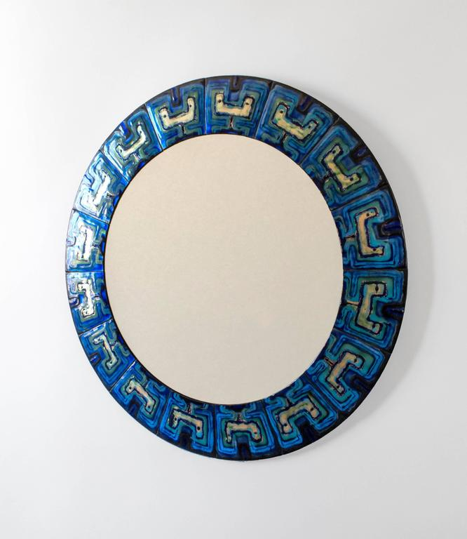 Composed of enameled copper plates hand-painted by the Danish artist Bodil Eje. The repeating pattern displays richly variegated blues enclosing colorless enamel reserves, surrounding a colorless glass mirror plate.