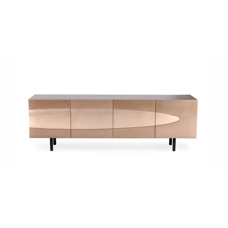 The Ellipse sideboard in bronze is an artistic luxurious piece built to satisfy bronze lovers. This four door, two-drawer contemporary cabinet is entirely clad in bronze, with a sleek Venetian red lacquered interior and genuine ebony legs.  This
