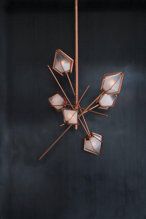 Elegant sculptural light-fixture inspired by jewelry design featuring a mold-blown glass gem in a chic metallic setting to create an asymmetrical starburst of light.  Harlow is available in various color ways, and held in a metallic frame