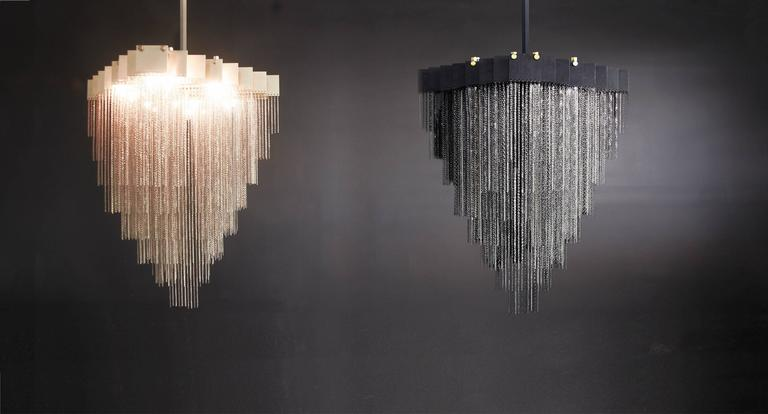 A bold and elegant sculptural light fixture, the Kelly chandelier holds over a half-kilometer of reflective chain to generate a staggered and diametrically exquisite geometrical form.   Light glimmers throughout the chain for to create a soft
