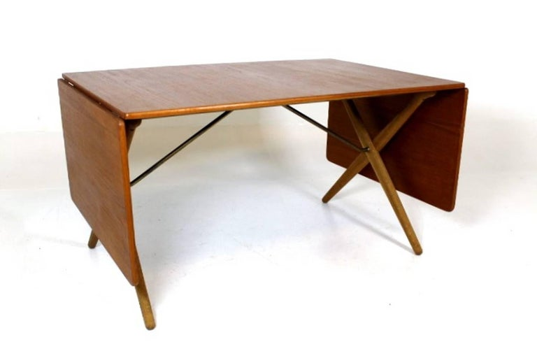 Great dining table, designed by Hans J. Wegner 1952, Model AT-309. Manufactured by Andreas Tuck. Top in teak and legs in solid oak with brass trust base. Stamped with designer and maker.  Measures: 128 + 50 + 50 = 228 cm long.