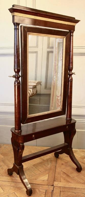 An elegant, 19th century, Italian cheval mirror made in both solid and veneered mahogany wood with hand-carved giltwood mouldings and ormolu fittings. Fitted with neat drawer at the mirror.