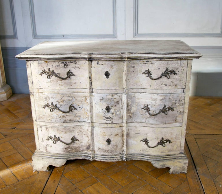 Hand-carved Louis XIV style Arbelette chest of drawers. Hand finished in a textured two tone patina of distressed paint work over silver gilding.