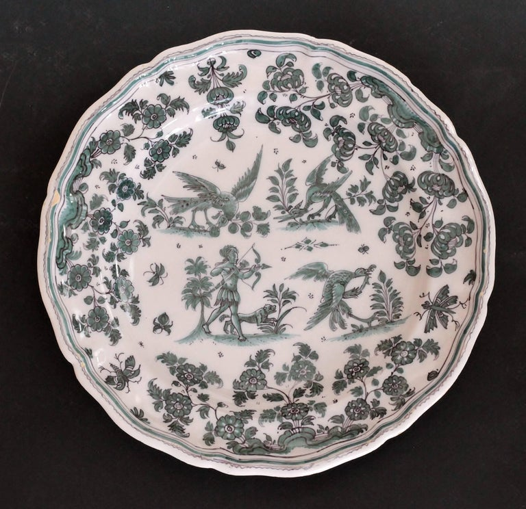 Earthenware plate decorated in shades of green of grotesque fantasy animals on four terraces surrounded by flowers and foliage Marked: