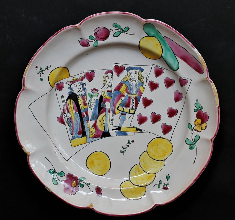 A plate in faience decorated with five playing card as a royal flush in the center, coins, token and flowers all round. South of France, perhaps Moustiers de Ferrat, 18th century. Measures: Diameter 24.5 cm., Height 3.2 cm. Several flakes of