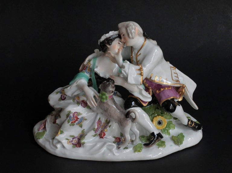 Gallant group in porcelain of Meissen (Germany, Saxe) a man and his lady seated together, a pug dog on the dress of the lady. Model of J.J. Kandler, circa 1746. Measures: Height 15 cm, depth 10 cm, width 15.7 cm