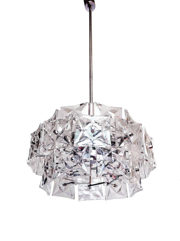 Three-tier chandelier with sculptural faceted crystals and chrome-plated frame made by Kinkeldey, Germany in the 1960s. The lamp takes one twelve small Edison base bulbs. The bar is divided and can be shortened.