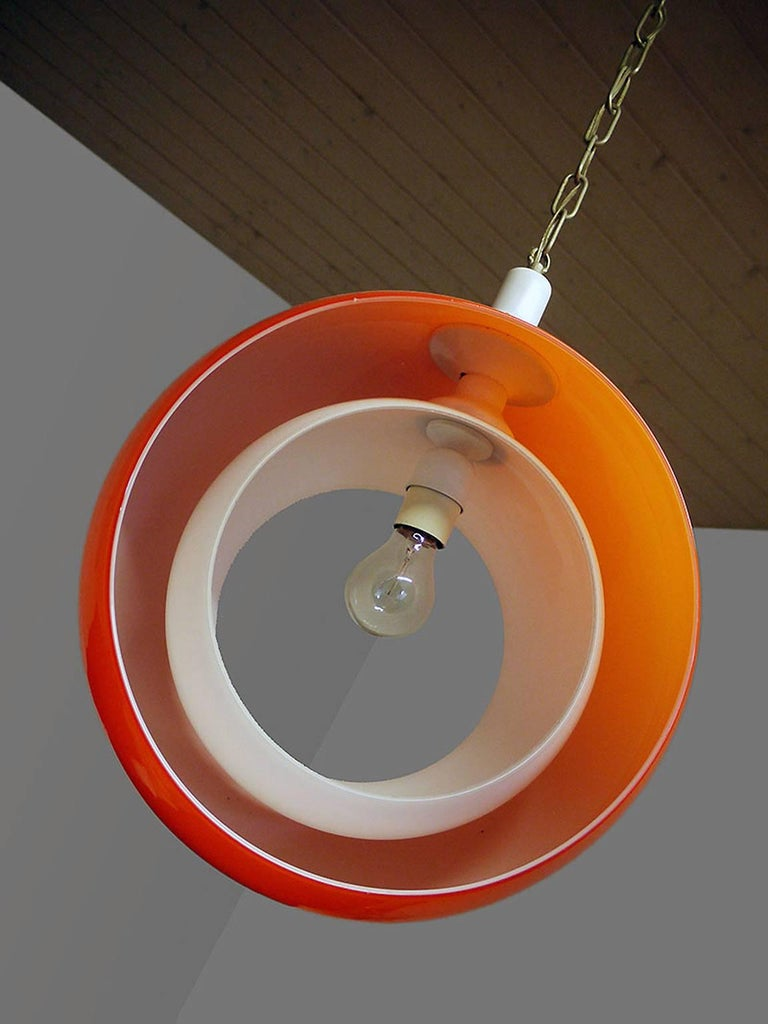 Murano glass pendant lamp by Carlo Nason for Mazzega, Italy with an orange glass globe and a white opaline glass moving part. Designed in the 1960s, Italy. The lamp takes one large Edison bulb. Measures: Diameter 15 in./ 38 cm Height 17.7 in. /