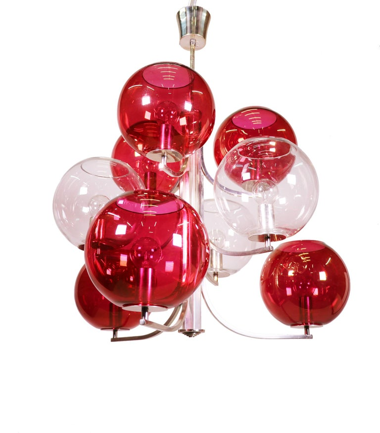 A cluster of gold tinted cranberry and clear glass globes on a silver plated frame made in Italy in the 1960s. A modern and glamorous statement chandelier for over a dining table.