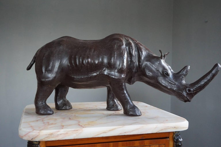 Good size and highly decorative rhinoceros sculpture.  This full-grown and impressive rhino has both great aesthetic and decorative value. Underneath the leather hide is a well carved wooden sculpture which is why this sizable rhino has such
