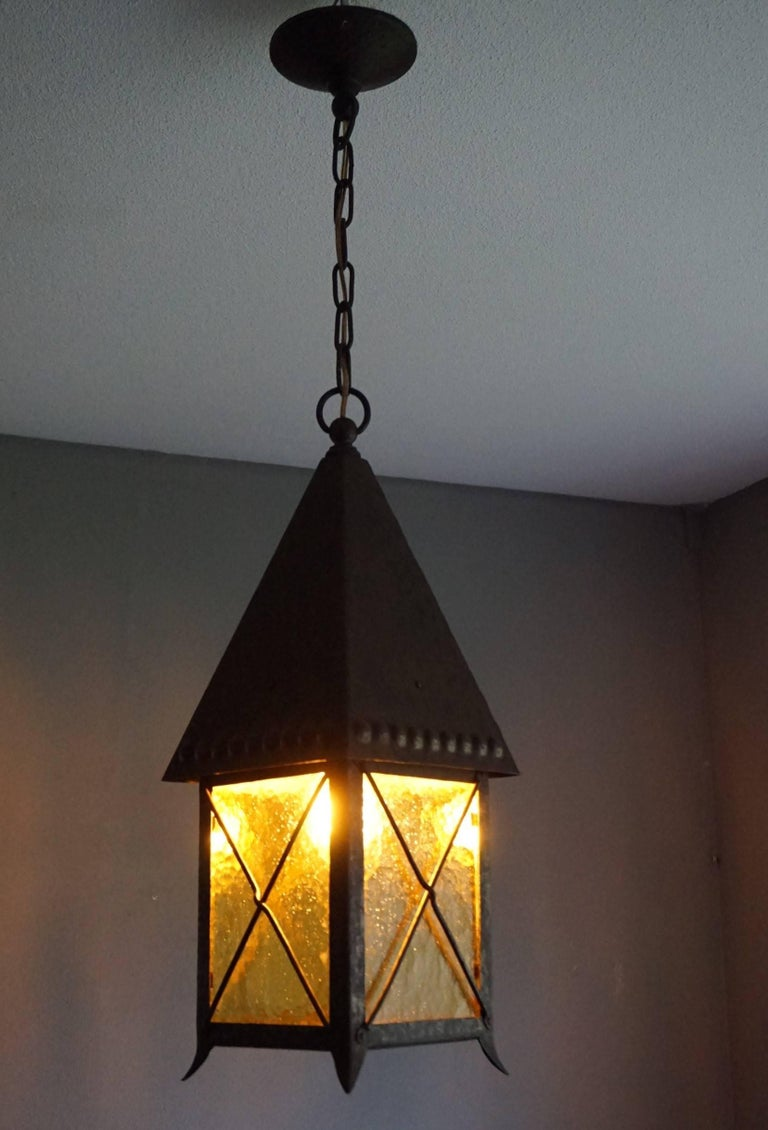One of a kind, hand-crafted pendant with original amber color glass.  If you live in an early 20th century house or appartment then this practical size and all hand-crafted, wrought iron pendant could be perfect for you. This fine example was made