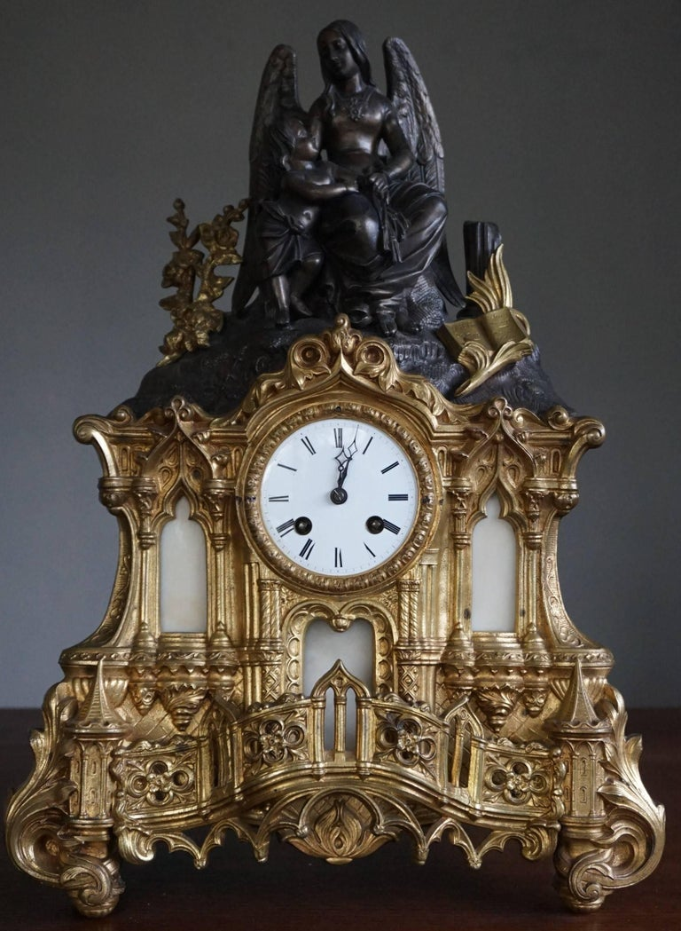 Cathedral design, gilt bronze and zinc clock.  This sizable, handcrafted, gracious and meaningful clock comes with a variety of Gothic church elements. As a matter of fact, the bottom half of this mantle clock very much resembles the entrance of a
