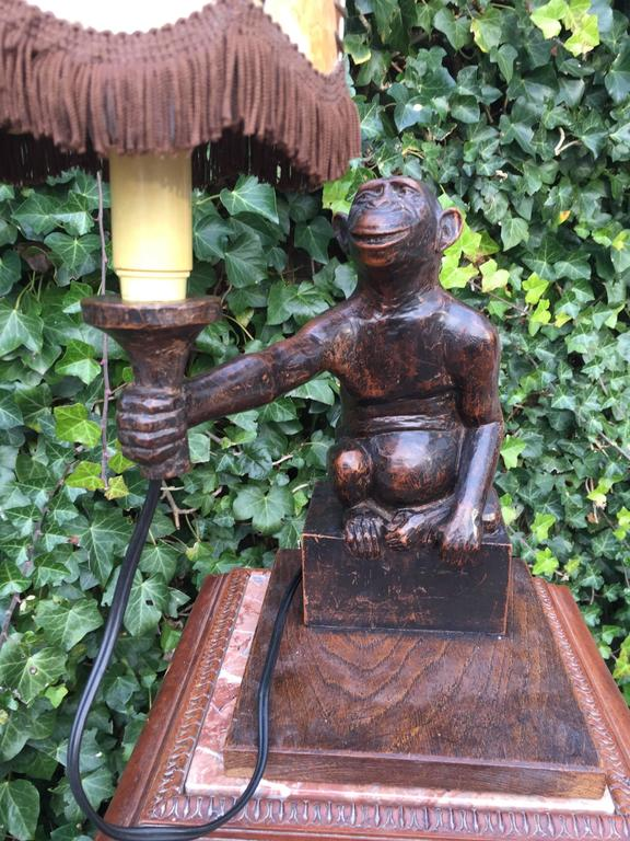 This monkey is looking for a new home!  Great antique, hand-carved monkey offering you his lamp. If you look closely than you can see him reaching out and offering the lamp to you, with a slight grin. This rare and delightful chimpansee desk or