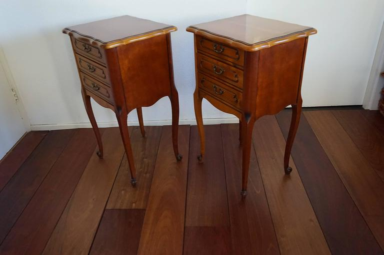 Elegant pair of French bedside cabinets.  These stylish nightstands were made in France by Sourisseau and we date them from the 1970s. They are in marvelous condition and as clean as one could hope. On either side of a box spring they will look
