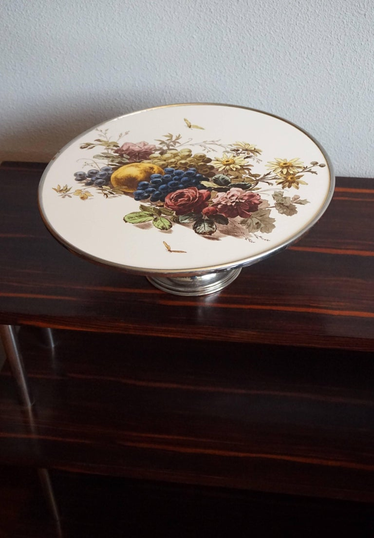 Handcrafted 1920s pie stand with beautiful decor.  This stylish and decorative pie stand from the 1920s is in very good condition. The shape of this wonderful stand is a joy to look at and the stunning decor of fruits and flowers really takes it to