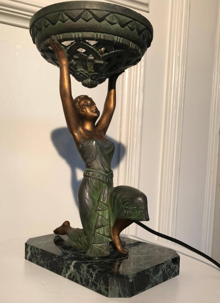 Egyptian revival Art Deco table lamp from circa 1925.  This beautifully patinated, sculptural lamp is still in wonderful condition. The metal female is dressed in the typical style of the roaring twenties. A period in which the global design