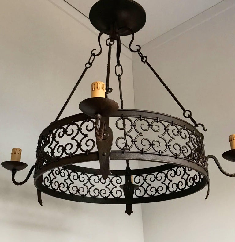 Quality crafted, forged in fire four light chandelier.  This good quality, hand-forged wrought iron chandelier comes with beautiful and artistic details which certainly lifts it above the average. In the right space it will look the business and we