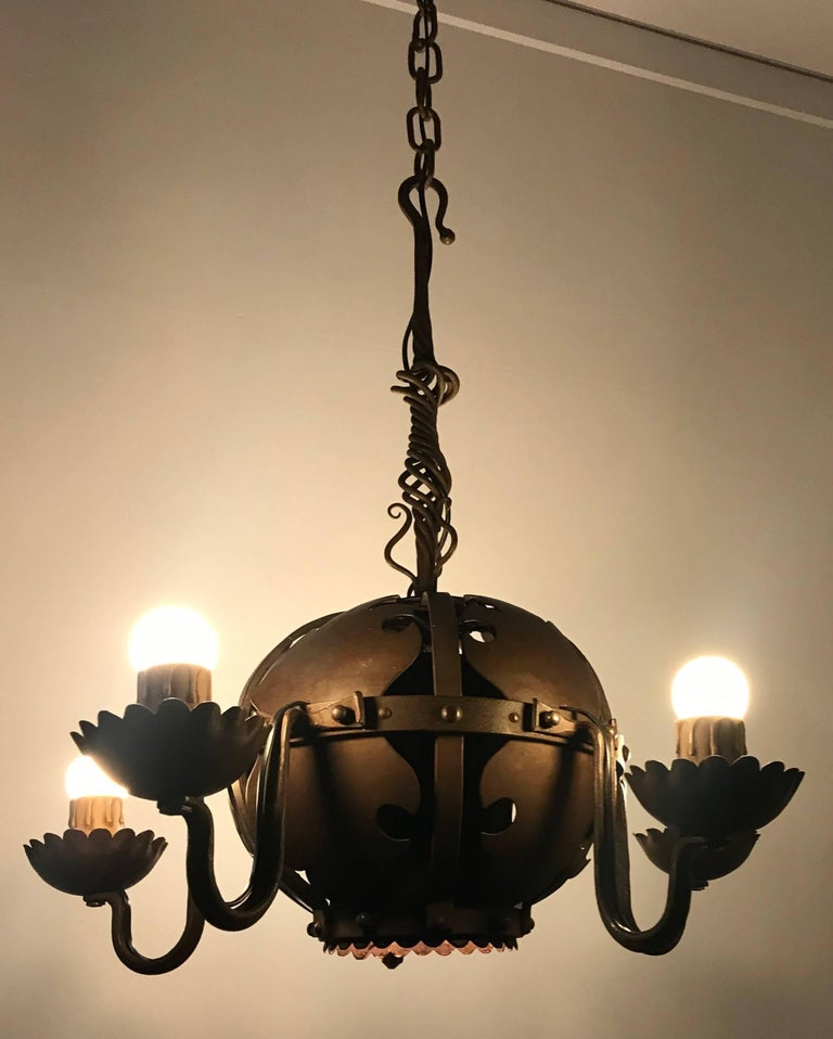 Rare design and quality crafted chandelier.  This artistic work of blacksmith lighting art is an absolute joy to watch and it is in excellent condition. The artistic details above and within the spherical centre definitely lifts it above the average