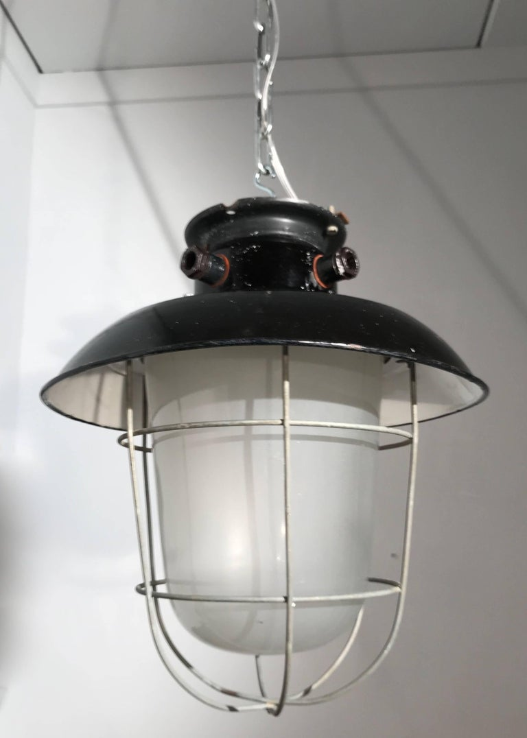 European 1920s Matching Pair of Industrial, Glass & Black Enamel Caged Light Pendant For Sale