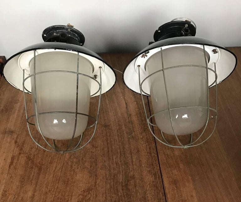 Original and great shape, industrial factory lamps.   This rare pair of industrial pendants with its original glass shades will look wonderful over a kitchen island, but we are certain that you too can think of many other places where this cool
