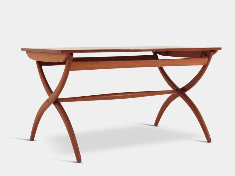 Ole Wanscher (1903-1985)  A danish midcentury classic by Ole Wanscher. This beatifully cut out wood coffee table in teak is with with adjustable height from 60-70 cm.  Manufactured by the great Rud Rasmussen in 1951.
