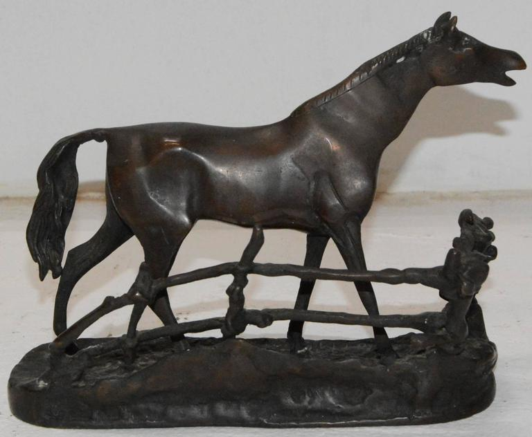 This cast bronze horse stands in a elongated stretched out pose. The details make this cast metal horse a piece you need for your collection. The horse is backed by a rustic, rambling fence.