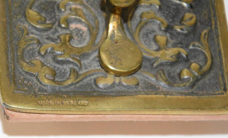 We are featuring an ornate Victorian inkwell with a rocking blotter. The details on the cast bronze are intricately woven in the cast bronze. Two porcelain cups are inside the lids. This would be a lovely set to rest upon your desk. Blotter