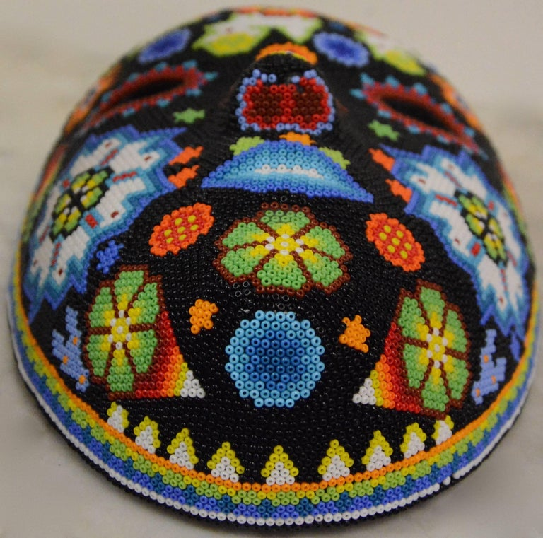 This is an intricate hand beaded Huichol Folk Art mask. The name of this mask is Peyote Blossom. The colorful mask features intricate tribal-like designs throughout that are comprised of glass beads in vibrant shades of red, orange, yellow, green,