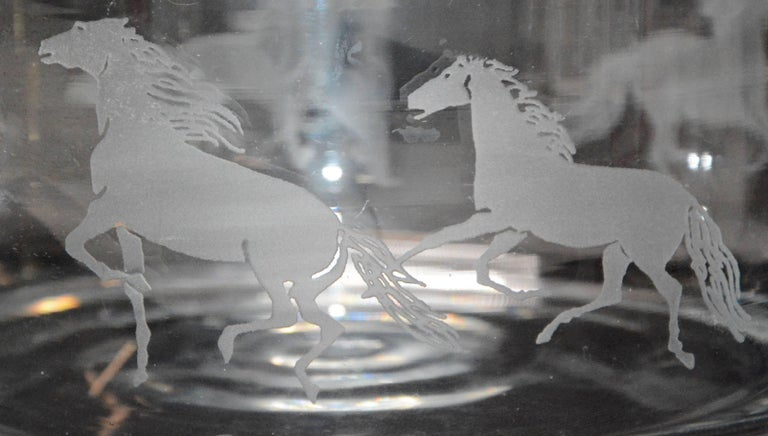This is a very heavy, clear glass bowl with prancing horses etched on the outer rim. The bowl is not marked. The glass thickness on the rim measures 7/16 of an inch.
