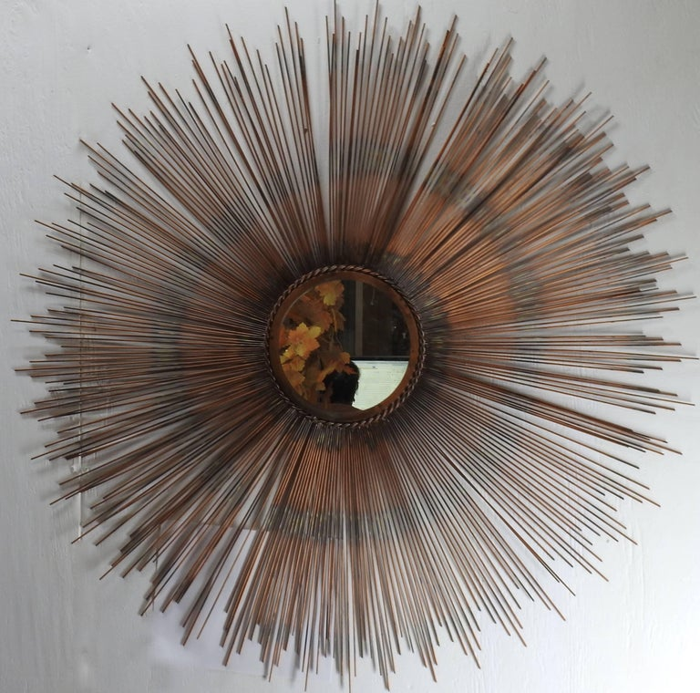 The sunburst on this stunning mirror showcases shades of copper on the metal. The mirror is framed with a twisted metal border. The centre mirror has a hanger mounted to the back which is finished with black felt.
